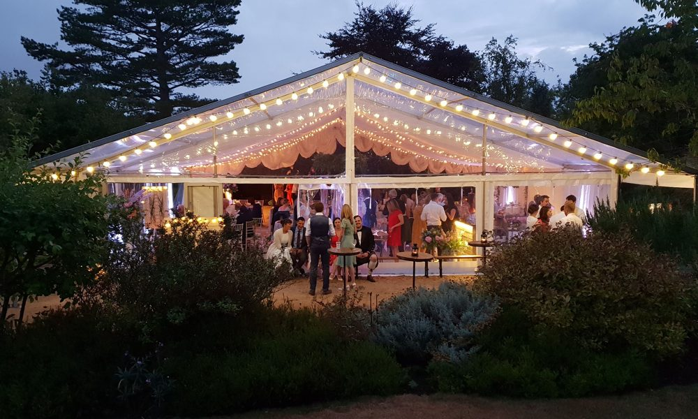A wedding evening party under a white marquee canopy
