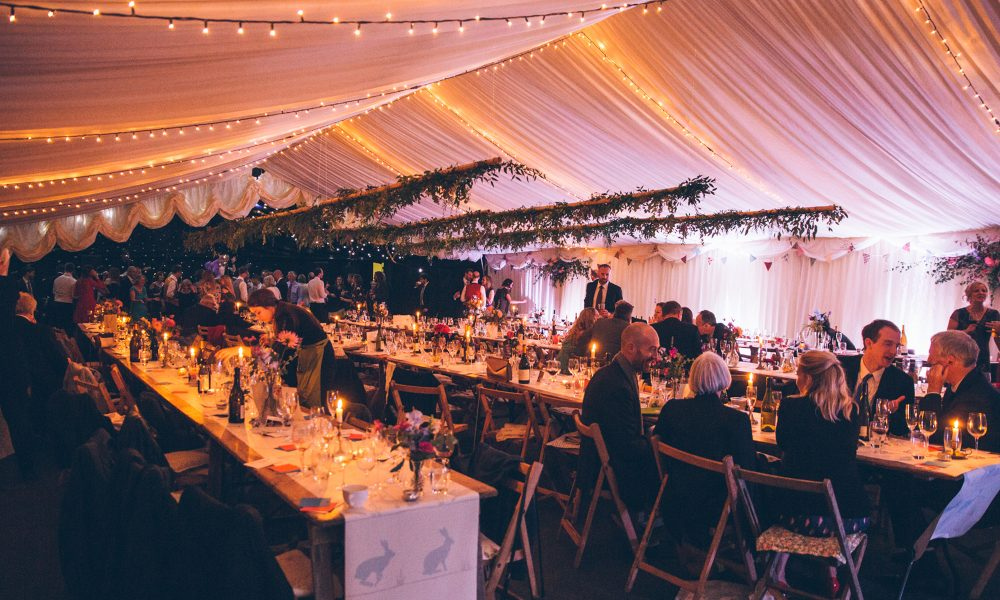 A dimly lit wedding reception inside a white marquee