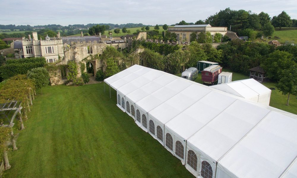 An expansive white marquee in the grounds of an old manor house