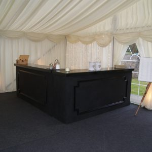 A black wooden reception counter with a table seating plan to the right