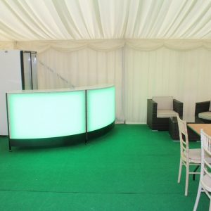 A colour-changing drinks bar in the corner of a white marquee, surrounded by table and chairs