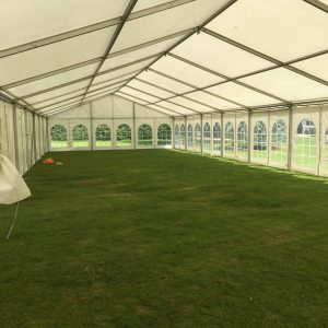 Inside a white marquee with windows on an area of grass