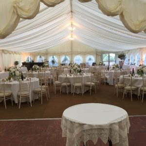 White wedding reception tables within a large white marquee