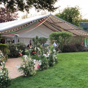 A white marquee with colourful trimmings hanging from the canopy