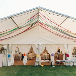 Entrance to a white marquee with colourful trimmings hanging from the canopy