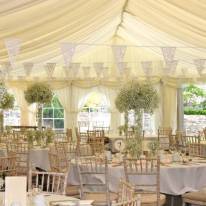 White bunting above wedding reception tables within a white marquee