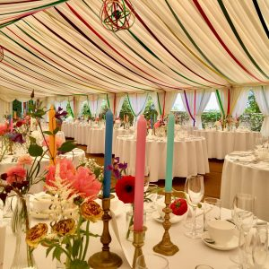 Inside a white marquee with colourful trimmings and candles in the foreground