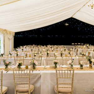 A white marquee wedding reception with lines of tables and black background