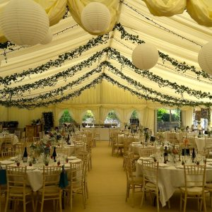 Inside a white marquee wedding reception with tables and ivy suspended from the ceiling