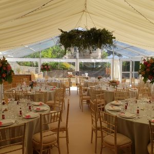 Inside a white marquee with tables and plants suspended from the ceiling