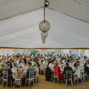 A crowded wedding scene inside a white marquee