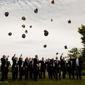 Men at a wedding tossing their hats into the sky