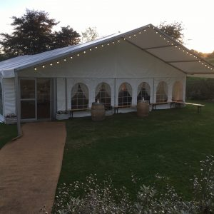 A white marquee with two barrels in front in the evening sun