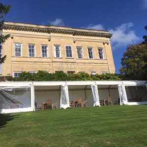 An old country manor house fronted by a white marquee and lawn in the foreground