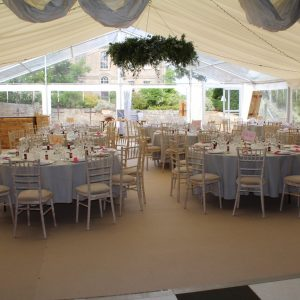 A white marquee with tables setup for a wedding reception