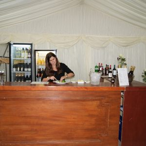 A waitress working behind wooden drinks bar inside a white marquee