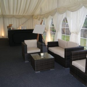 Inside a white marquee, a drinks bar in the far corner and comfy seating in foreground