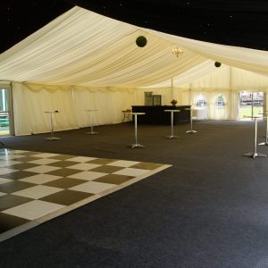 Inside a white marquee, a drinks bar in the far corner and dance floor in foreground