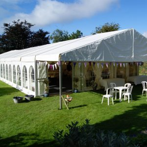 A white marquee with pastel coloured bunting surrounding the entrance in a green field