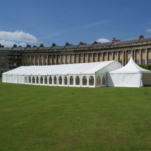 A white marquee in a green field with iconic Bath buildings in the background