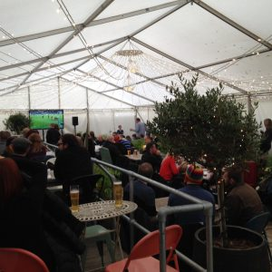 Inside a white marquee with people enjoying drinks and watching Football