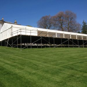 A white marquee built on top of scaffolding in a green field