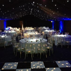 A wedding reception at night with dance floor in foreground and spot lighting