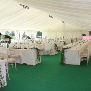 Inside of a white marquee with green carpet, setup for a wedding reception