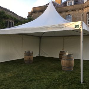 A peaked white marquee with three old barrels for tables