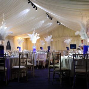 Tables with feathers on them inside a white marquee at a wedding