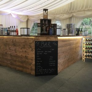 A wooden drinks bar in the corner of a white marquee with drinks menu in the middle