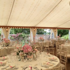 A white table with pink flowers at a wedding reception