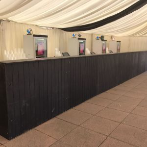 A white marquee on concrete paving and a drinks bar with cashiers