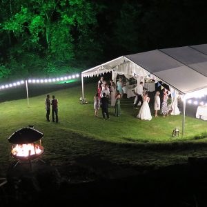 A night time wedding reception with a fire pit in foreground