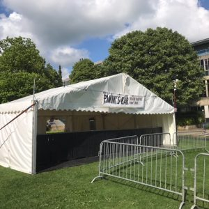 A marquee drinks bar on green grass with metal fencing outside