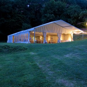 A white marquee in the early evening light, lit up by internal lighting