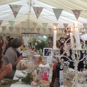 Inside a white marquee with floral bunting and flowers on tables