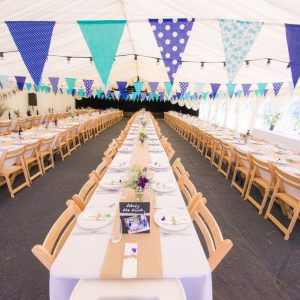 A colourful bunting display inside a white marquee with rows of tables