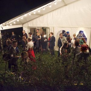 Guests enjoying a wedding outside the marquee at night