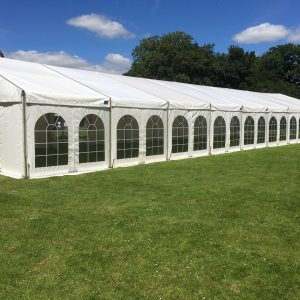 Outside a white marquee with 18 windows in a field