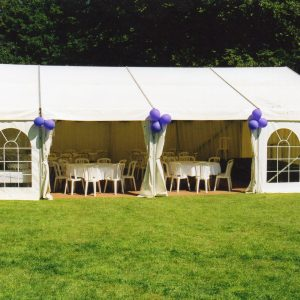 A white marquee with purple balloons