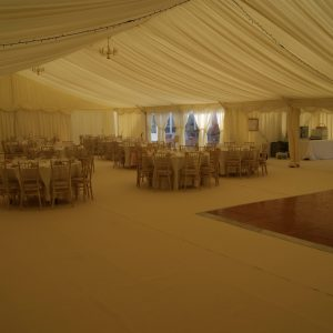 Dimly lit evening wedding reception white marquee