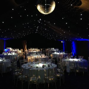 Inside a wedding marquee, dark with a disco ball in centre-top