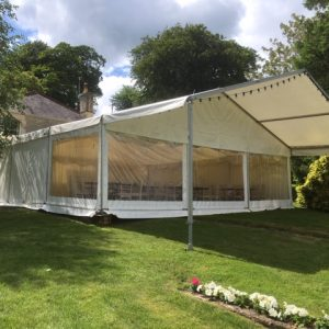 A white wedding marquee with canopy outside creating shade