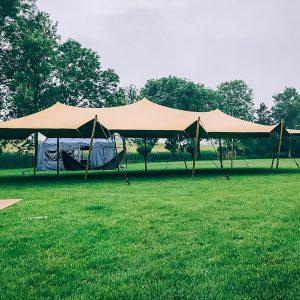 A light orange stretch tent setup in a green field