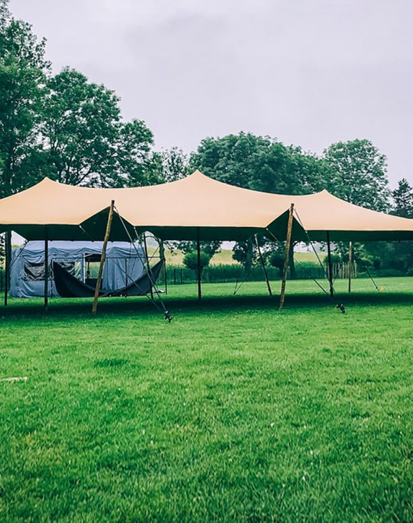 A light orange stretch tent setup in a green field