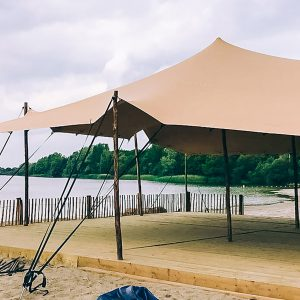 A light orange stretch tent setup on a beach waterside