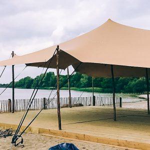 A light orange stretch tent setup on a beach waterside